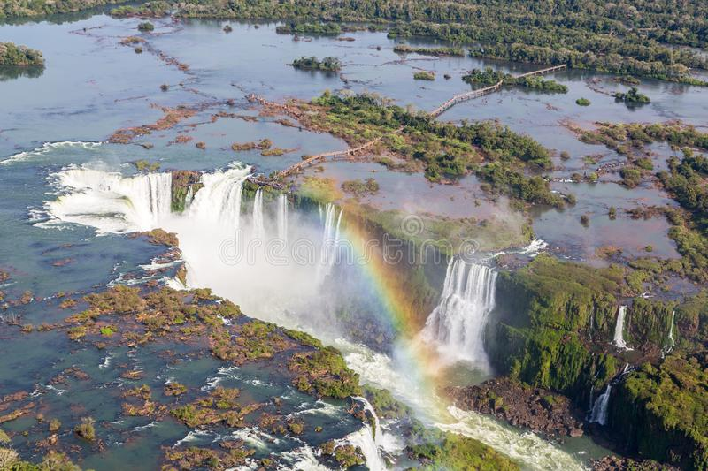 Aerial bird`s-eye view of beautiful rainbow above Iguazu Falls Devil`s Throat chasm from a helicopter flight. Brazil and Argentina royalty free stock image