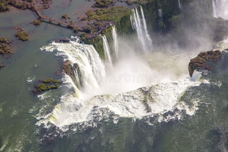 Aerial bird`s-eye view of beautiful rainbow above Iguazu Falls Devil`s Throat chasm from a helicopter flight. South America. stock images
