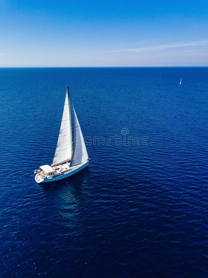 Aerial view from drone of white yacht in deep blue sea royalty free stock image