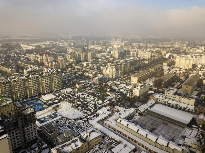 Aerial black and white winter top view of modern city center with tall buildings and parked cars on snowy streets.  royalty free stock photo