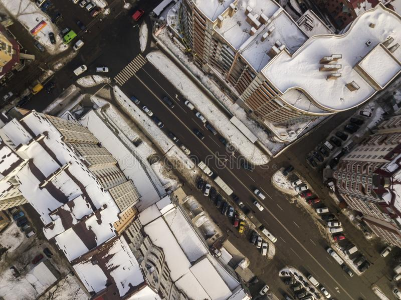 Aerial black and white winter top view of modern city with tall buildings, parked and moving cars along streets with road marking. Urban cityscape, view from royalty free stock photos