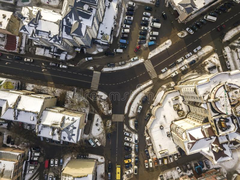 Aerial black and white winter top view of modern city with tall buildings, parked and moving cars along streets with road marking royalty free stock photos