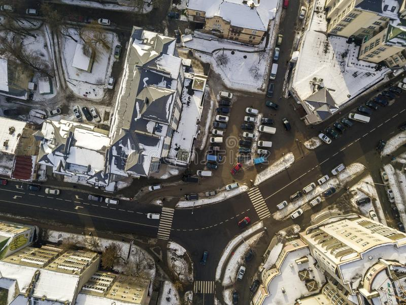 Aerial black and white winter top view of modern city with tall buildings, parked and moving cars along streets with road marking stock image