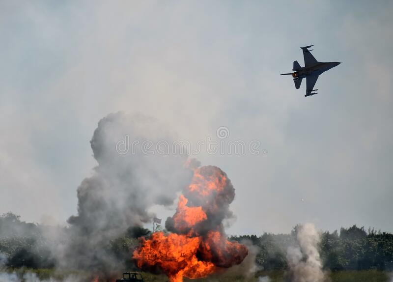 Aerial bombardment and fiery explosion below stock photo