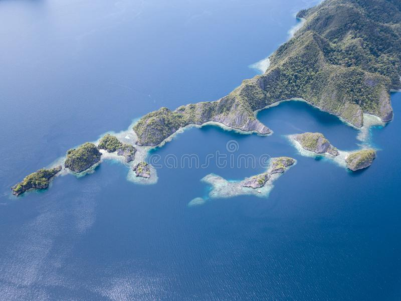 Aerial of Calm Seas and Islands in Raja Ampat. The limestone islands of Misool, Raja Ampat are surrounded by healthy, shallow coral reefs. This remote region in royalty free stock images