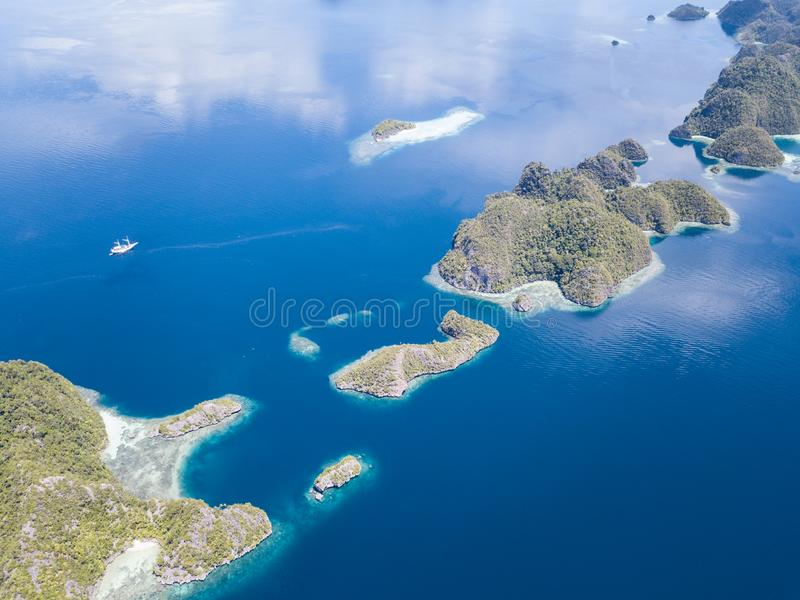 Aerial of Calm Seas and Limestone Islands in Raja Ampat. The limestone islands of Misool, Raja Ampat are surrounded by healthy, shallow coral reefs. This remote stock photography