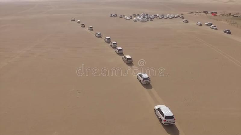 AERIAL: cars driving through desert. Stock. Aerial view of 4x4 off road land vehicle taking tourists on desert dune. AERIAL: cars driving through desert. Aerial royalty free stock photography