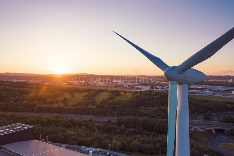 Aerial close up shot of a wind turbine in front of a perfect sunset royalty free stock images