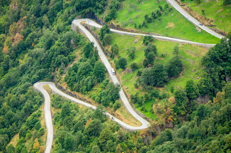 Aerial close-up view of a zig-zag winding road going up a steep slope near Geiranger, Norway. With a big bus going up stock images