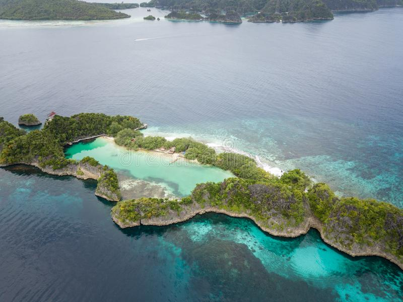 Aerial of Coral Reef and Rock Island in Raja Ampat. A beautiful limestone island is fringed by a healthy coral reef in Raja Ampat, Indonesia. This remote region royalty free stock photography