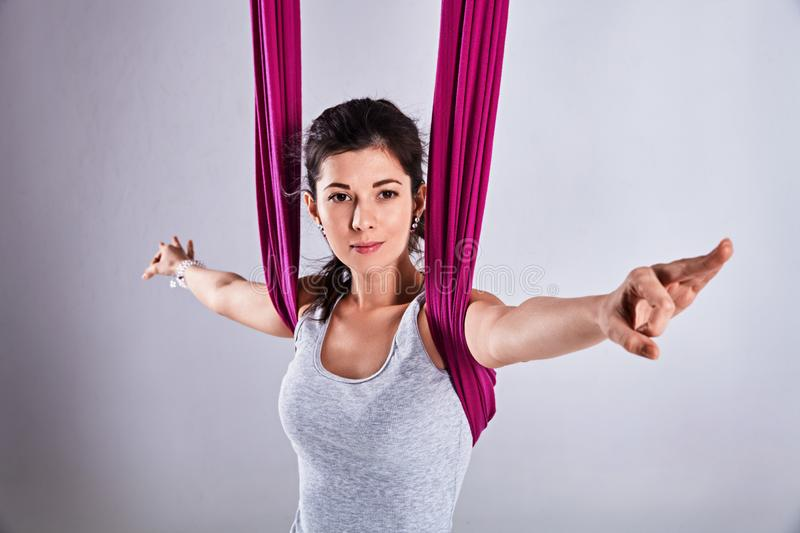 Aerial different inversion antigravity yoga in a hammock. Young woman practices aerial different inversion antigravity yoga with a hammock in a white studio royalty free stock photos
