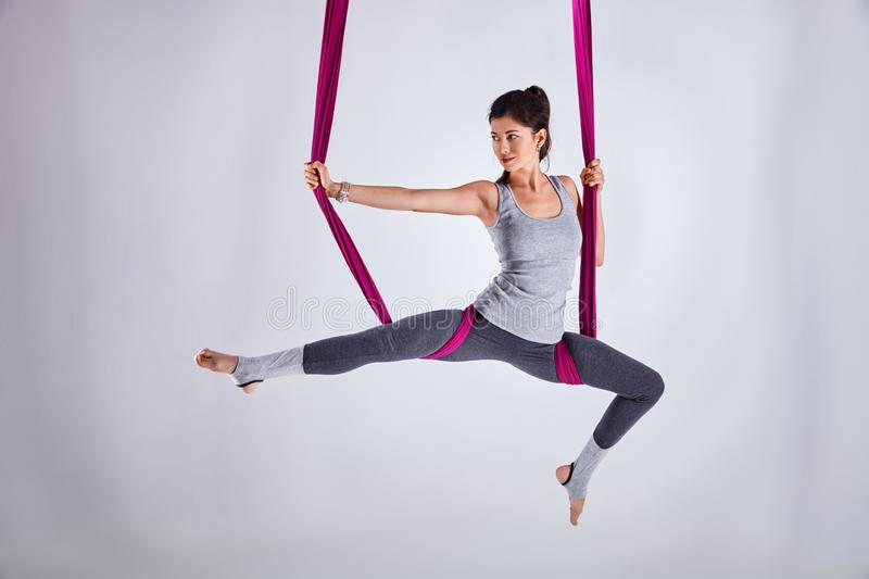 Aerial different inversion antigravity yoga in a hammock. Young woman practices aerial different inversion antigravity yoga with a hammock in a white studio stock image
