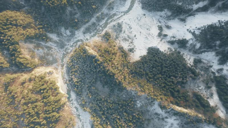 Aerial down view of a snowy river valley in northern mountains of Italy stock photo