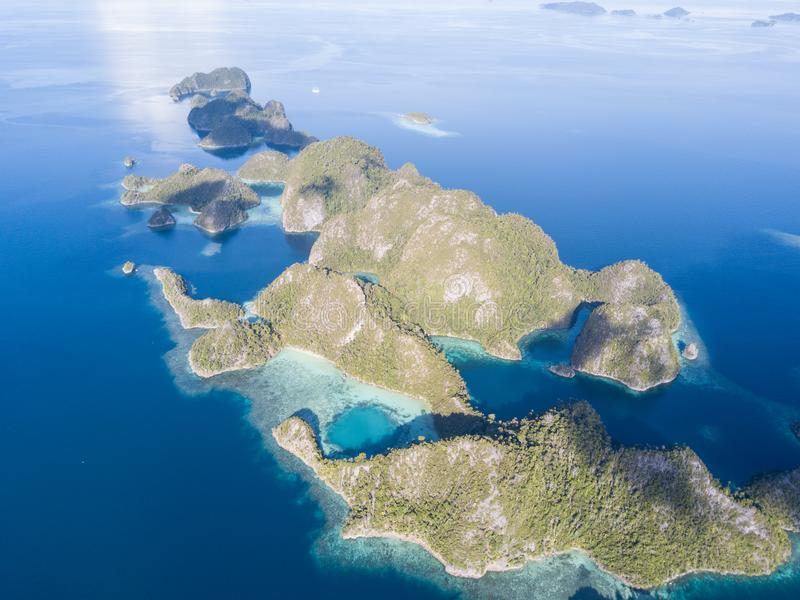 Aerial of Dramatic Limestone Islands in Raja Ampat. The limestone islands of Raja Ampat are surrounded by healthy, shallow coral reefs. This remote region in stock photography