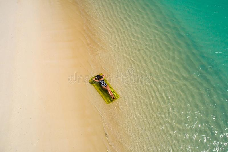 Aerial drone aerial view of Beautiful girl having fun on the sunny tropical beach. Seychelles royalty free stock photography