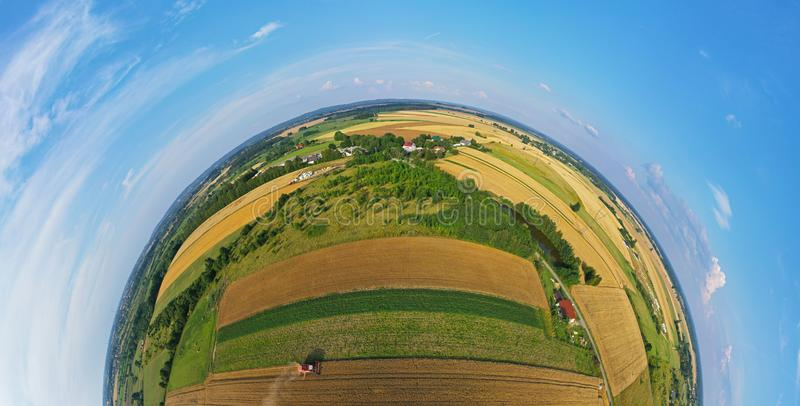 Aerial drone 180 degree rounded view on red harvester during wheat field harvesting, collecting seeds, making dust cloud, driving royalty free stock images