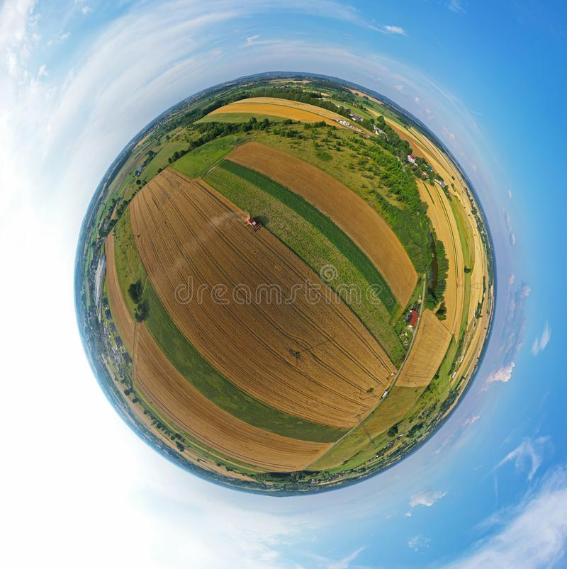Aerial drone 360 degree spherical tiny planet view on red harvester during wheat field harvesting, collecting seeds, making dust royalty free stock photos