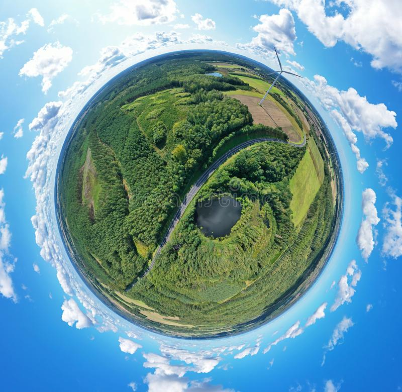 Aerial drone 360 degree view on wind turbine, snake shape road, wheat fields and forest during summer stock photo