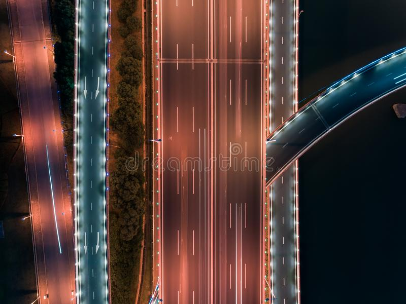 Aerial drone flight over night road traffic. Two-level road junction. Top view. stock photos