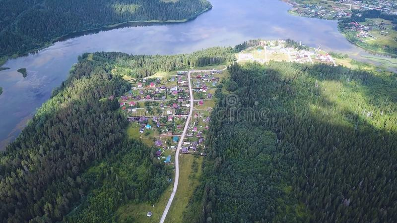 Aerial Drone Footage View: Flight over autumn village with road at rhe middle of the forest. Clip stock photography