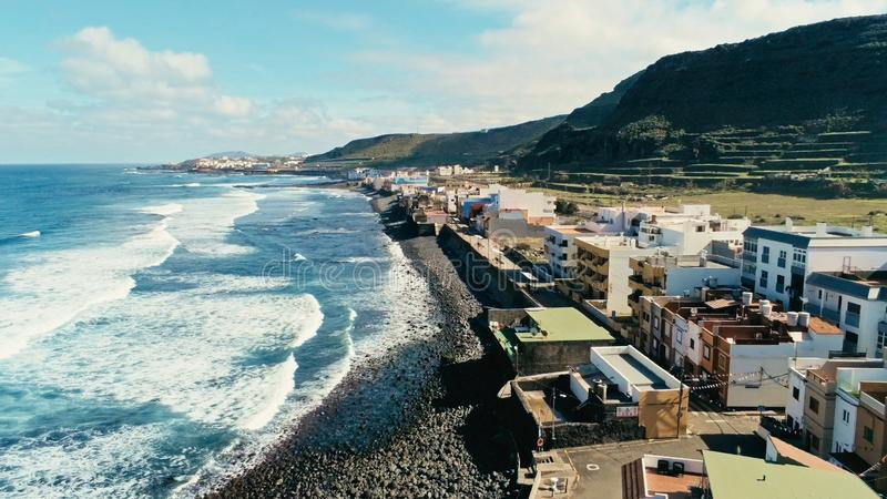 aerial drone i beautiful stunning surf beach with waves and swell coming in in front of a traditional tiny cute village high cliff stock photos