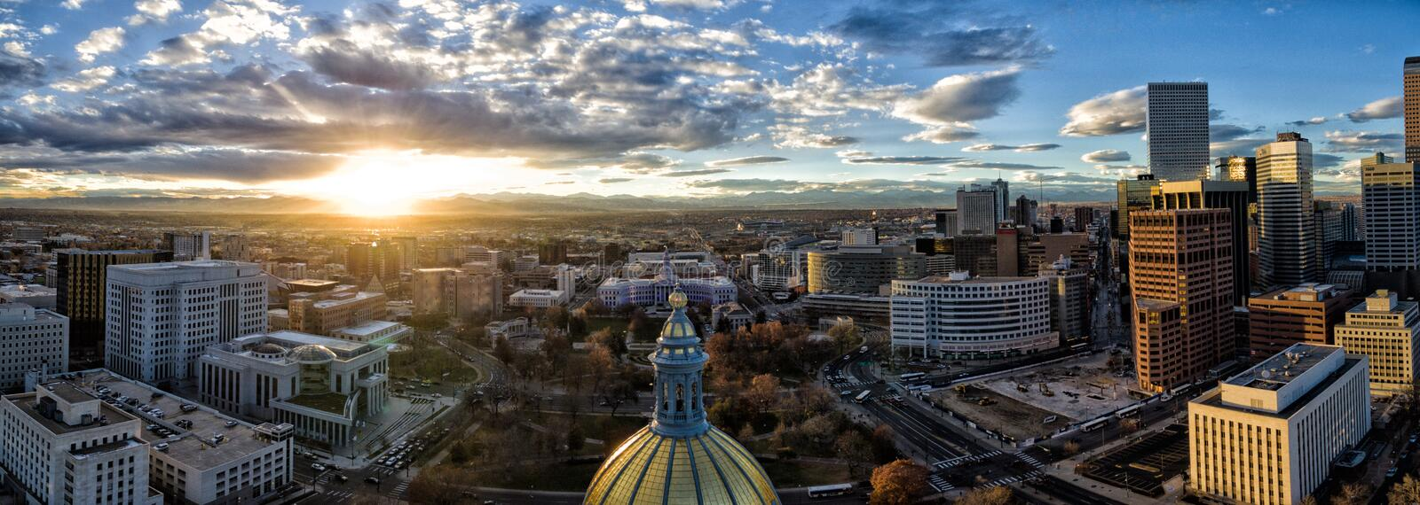 Aerial Drone Panorama - Stunning golden sunset over the Colorado state capital building & Rocky Mountains, Denver Colorado. Stunning sunset over the golden stock photo