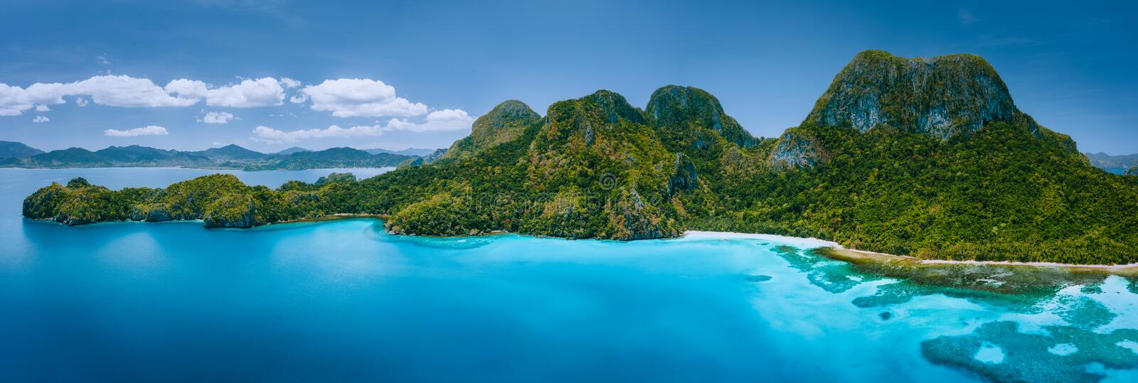 Aerial drone panoramic view of uninhabited tropical island with rugged mountains, rainforest jungle, sandy beaches. Surrounded by blue ocean royalty free stock photos