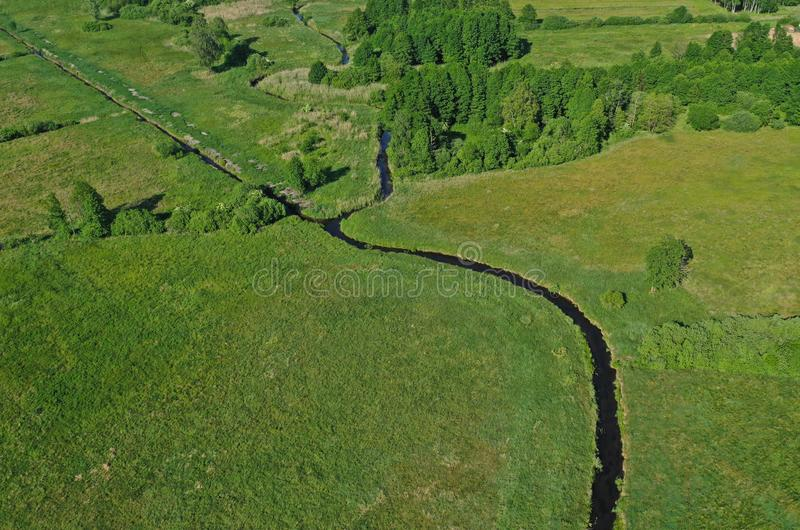 Aerial drone perspective view on european green meadows and forest divided by snake like river royalty free stock photo