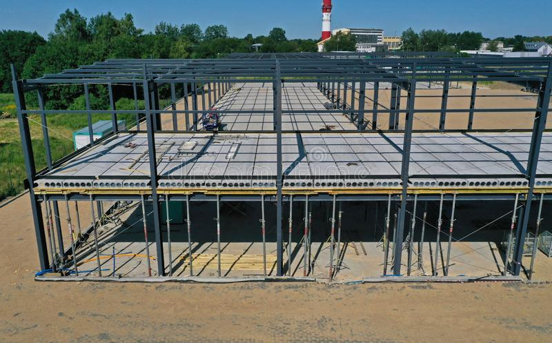 Aerial drone perspective view on steel construction frame, on building site, concrete floor with metal pipe supports and brick stock images