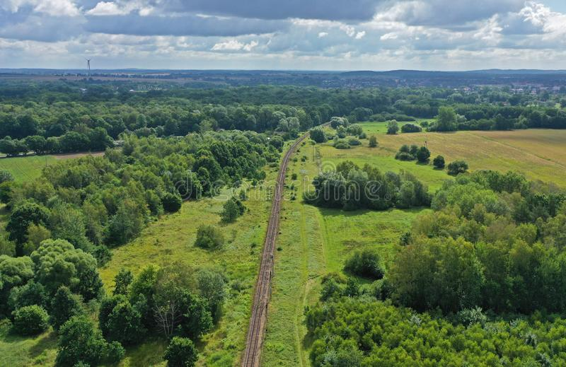 Aerial drone perspective view on straight curved railroad in rural scenery with green forest during summer stock photos