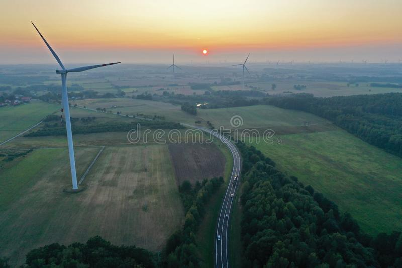 Aerial drone perspective view on wind turbine, snake shape road, wheat fields and forest during summer sunset royalty free stock image