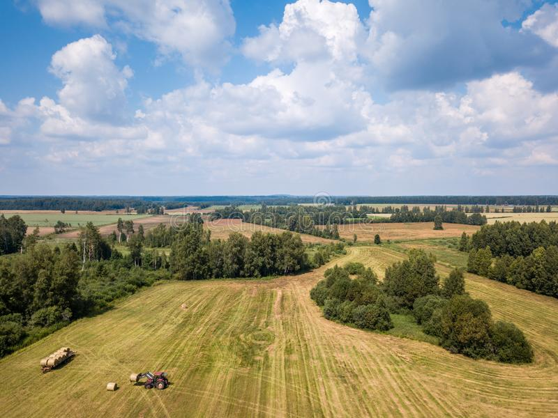 Aerial Drone Photo of Farmer Harvesting Hay Rolls in the Wheat F stock image