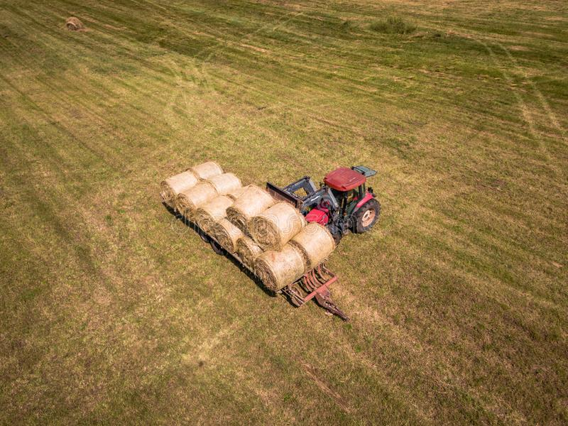 Aerial Drone Photo of Farmer Harvesting Hay Rolls in the Wheat F stock photo