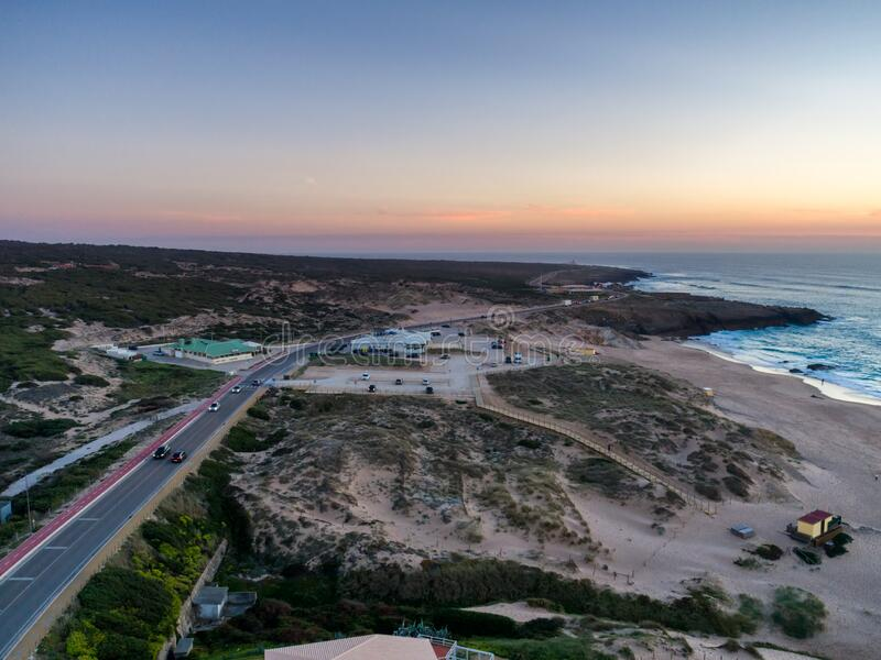Aerial drone photo of Praia do Guincho beach sand dunes and the coastline at sunset, in Portugal. Aerial drone photo of Praia do Guincho beach sand dunes and the stock photography