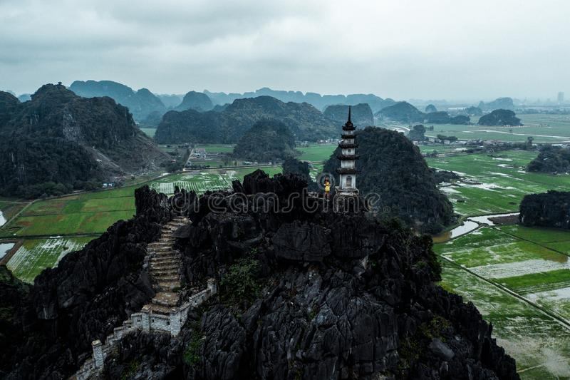 Aerial drone photo - Woman next to a shrine atop a mountain in northern Vietnam.  Hang Mua. Aerial drone photo - Woman next to a shrine atop a mountain in stock photography