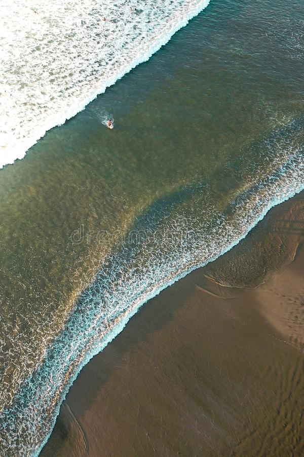 Aerial of waves hitting the beach at sunset stock images