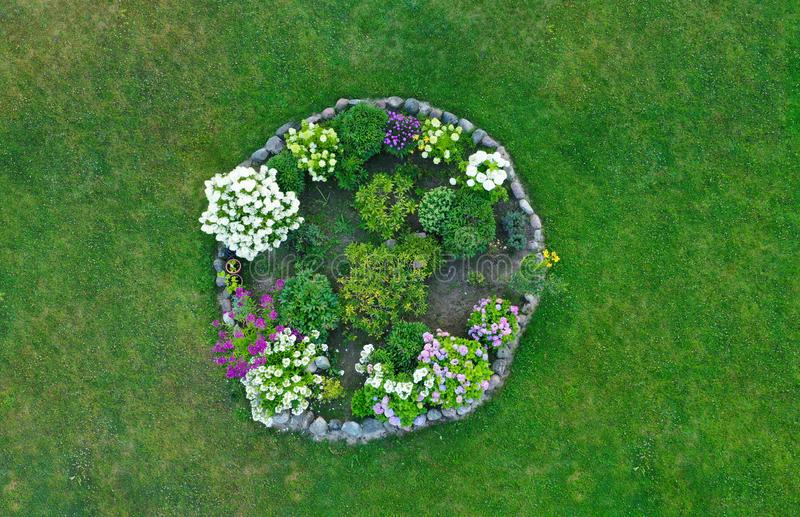 Aerial drone top down view on stylish round flowerbed surrounded by rock wall with violet, white and yellow blooming flowers. stock images