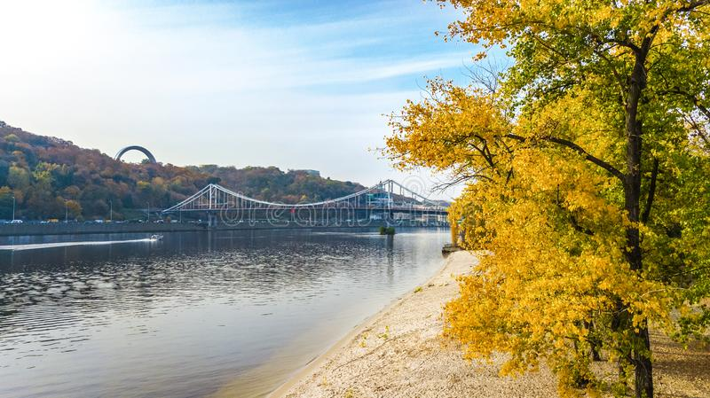 Aerial drone view of autumn pedestrian Park bridge, yellow fall trees, Truhaniv island, Dnieper river and Kyiv cityscape. From above, city of Kiev, Ukraine stock photos