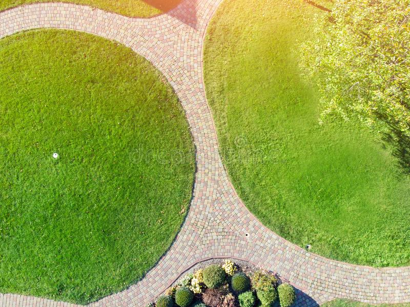 Aerial drone view of backyard garden with circle wath path, green grass lawn and trees. Landscape design and gardening royalty free stock photo