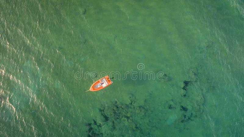 Aerial drone view of beautiful clean waters in Corfu Greece and an isolated orange boat.Copy space. Horizontal stock photo