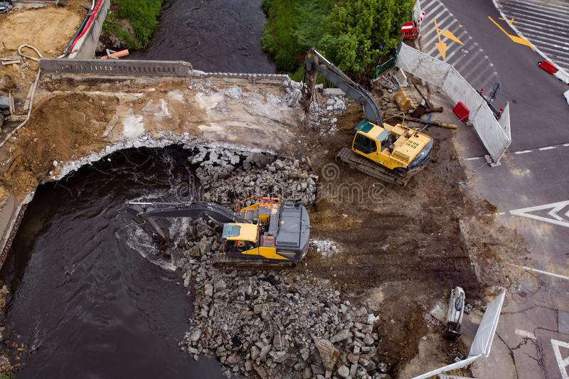 Aerial drone view on excavators demolishing a road bridge. Heavy machinery stock images