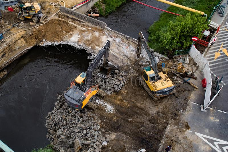 Aerial drone view on excavators demolishing a road bridge. Heavy machinery stock photos