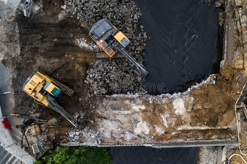 Aerial drone view on excavators demolishing a road bridge. Heavy machinery stock image
