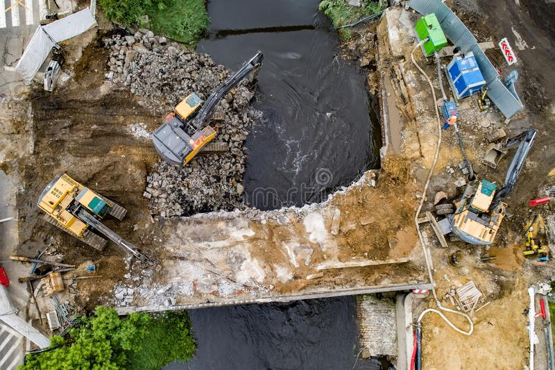 Aerial drone view on excavators demolishing a road bridge. Heavy machinery royalty free stock image