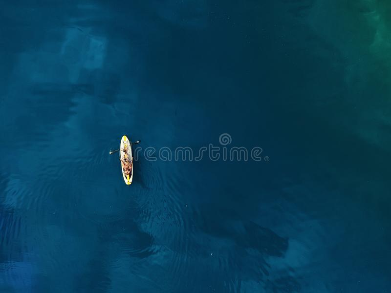 Aerial drone view of family having fun swimming on SUP stand up paddle inflatable surf board. Mother with children enjoy sitting. On surfboard at clear blue royalty free stock photos