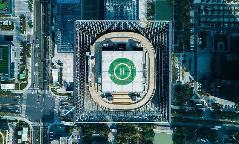 Aerial drone view of helipad on the roof of a skyscraper iin downtown with cityscape view on sunny day stock photography