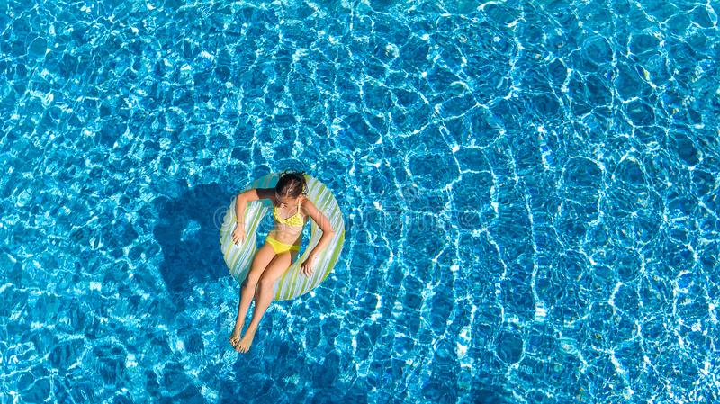 Aerial drone view of little girl in swimming pool from above, kid swims on inflatable ring donut , child has fun in blue water royalty free stock photo