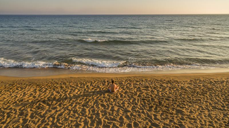 Aerial drone view of a lone man relaxing on a quiet beach just before sunset. Amazing Greece stock photos