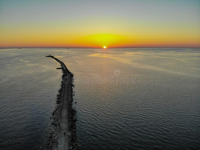 Aerial drone view of a long breakwater and sunset.  royalty free stock photo