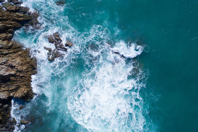 Aerial view of ocean`s beautiful waves and rocky coast. Aerial drone view of ocean`s beautiful waves crashing on the rocky island coast royalty free stock photography